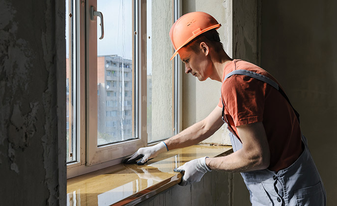 A Workman Replacing a Window